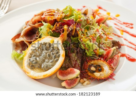salad with bacon and exotic fruits - stock photo