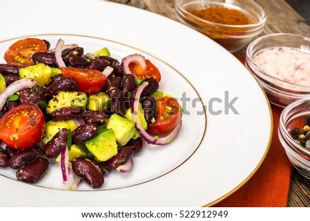 Salad with beans and avocado on background of old boards. Studio Photo