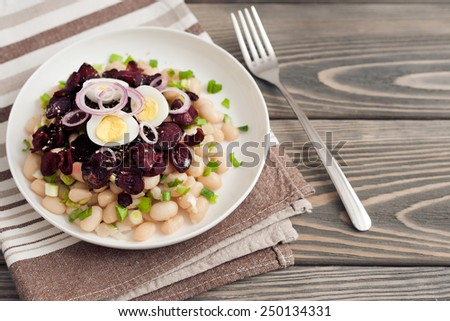 salad with beans, beetroot, egg, green onions on wooden background. - stock photo
