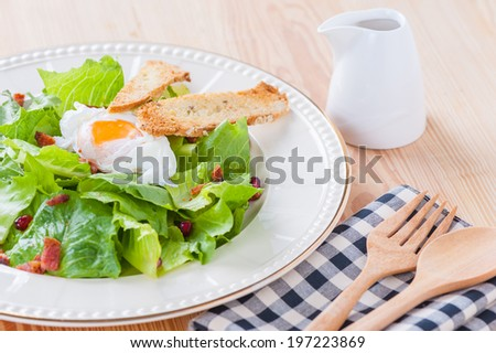 Salad with boiled egg, bacon and bread