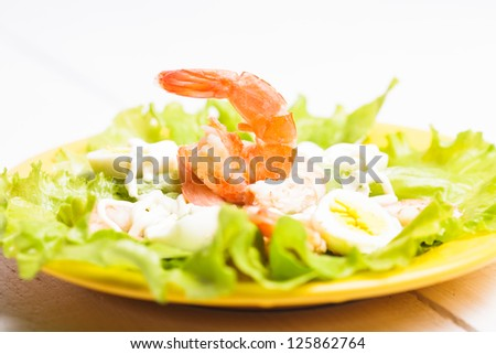 Salad with boiled shrimps, quail eggs and sauce