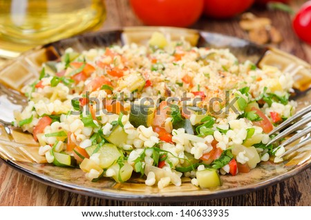 salad with bulgur, zucchini, tomatoes, chili peppers and parsley close-up - stock photo