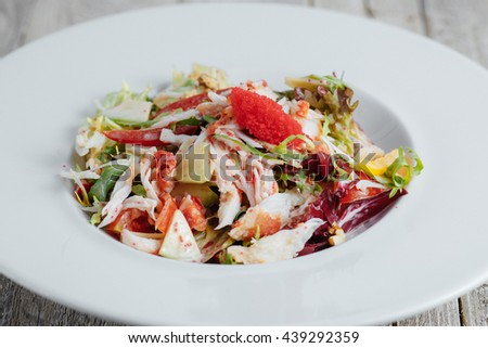 Salad with caviar, cheese, pepper and herbs in a white plate