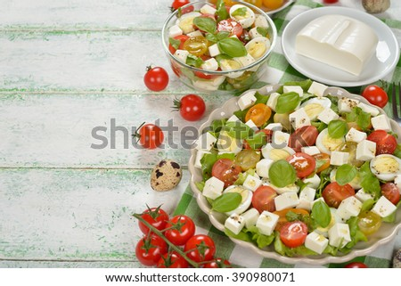 Salad with cherry tomatoes, eggs and cheese on white background