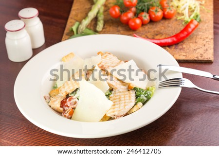 Salad with chicken, tomatoes and parmesan cheese on wooden table