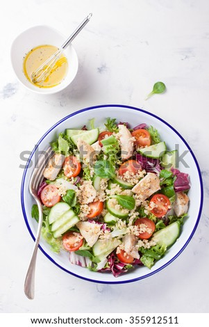 Salad with chicken, vegetables, bulgur and olive oil in an enamel plate. top view