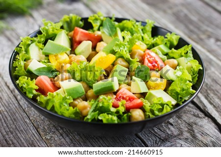 Salad with chickpeas, tomato and avocado, selective focus - stock photo