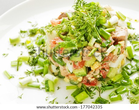 Salad with cod-liver, eggs, vegetables and greens. Shallow dof. - stock photo