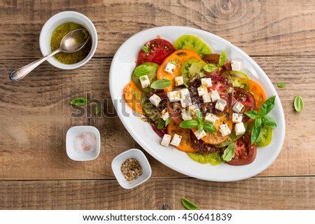 Salad with colorful tomatoes with cheese and pesto, selective focus - stock photo