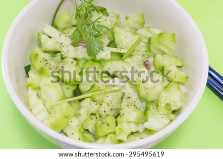 Salad with cucumber and marrow squash with parsley onion next to japanese chopsticks on a green background served - stock photo