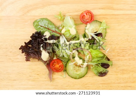 Salad with dressing and salad cream on a wooden board - stock photo