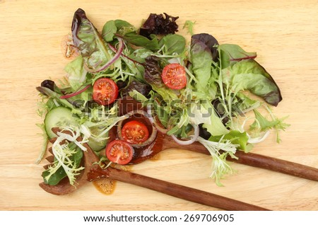 Salad with dressing and wooden salad servers on a wooden board - stock photo
