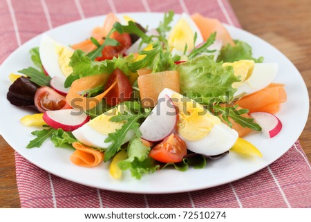 Salad with eggs, cherry tomatoes, radish, carrot and yellow bell pepper. Shallow DOF - stock photo