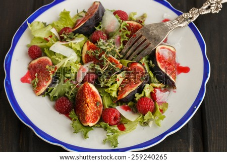Salad with figs and raspberries, dressed with raspberry sauce and Parmesan cheese - stock photo