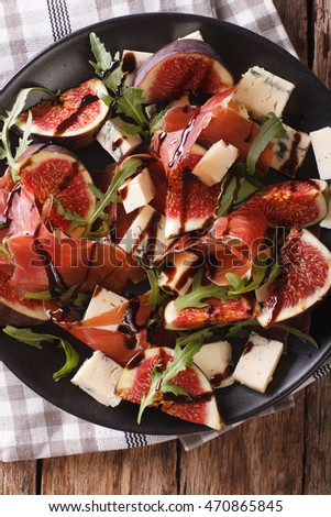Salad with figs, prosciutto, cheese and arugula close-up on a plate on the table. vertical view from above