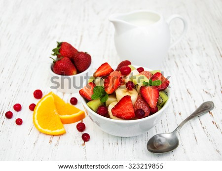 Salad with fresh fruits on a old wooden background - stock photo