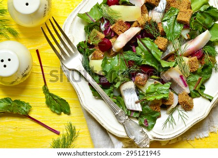 Salad with fresh organic beetroot,herrings and rye croutons on yellow wooden table. - stock photo