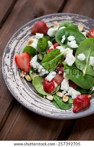 Salad with fresh spinach, strawberry and cheese, selective focus - stock photo