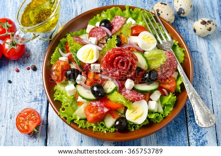 Salad with fresh vegetables, feta cheese, quail eggs, olives and salami. Plate with salad on a blue wooden background