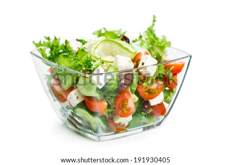 Salad with fresh vegetables in a glass bowl isolated on white background - stock photo