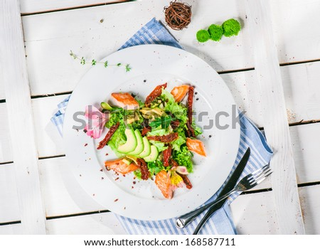 Salad with fried salmon, avocado and smoked tomatoes - stock photo