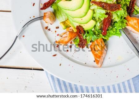 Salad with fried salmon, avocado and smoked tomatoes - stock photo