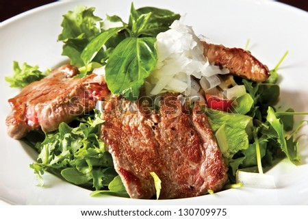 Salad with fried veal filet and champignons. Fried veal filet, champignons, light-green mix, Mikado tomatoes, cucumber, Parmezan cheese - stock photo