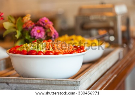 Salad with grape tomatoes, carrots and celery on a buffet table - stock photo