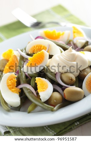 Salad with green bean, olives, onion, and boiled egg