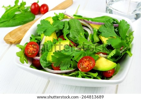 Salad with greens, avocado, cherry tomatoes, and red onions in bowl on white wood table - stock photo