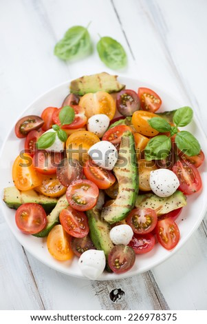 Salad with grilled avocado, tomatoes and mozzarella, close-up - stock photo