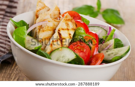 Salad with grilled chicken in a white bowl. Selective focus