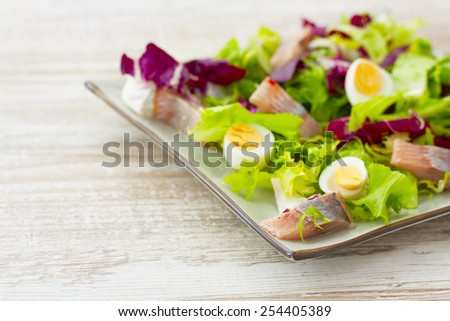 salad with herring, fresh herbs and quail eggs on a light wooden background - stock photo