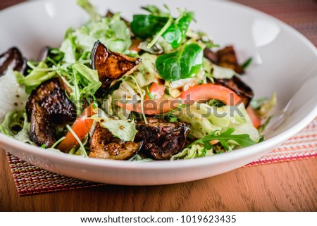 Salad with liver and eggplant on wood table. Closeup