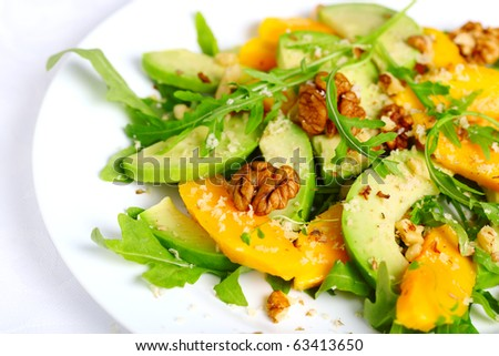 Salad with mango, avocado, arugula and walnuts - stock photo