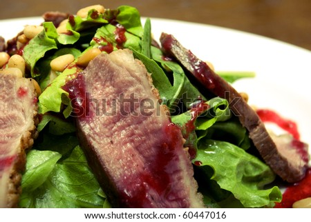 Salad with meat and pine nuts on white plate
