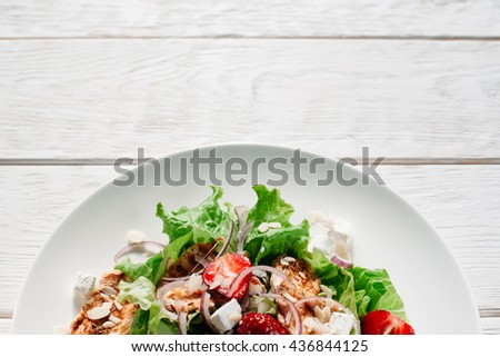 Salad with meat, strawberry, lettuce and feta cheese copyspace. Top view on portion of salad with small meat steaks, strawberries, lettuce and feta cheese. Flat lay on white wooden background - stock photo
