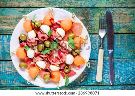salad with mozzarella, prosciutto, melon and olives with balsamic sause and basil - stock photo
