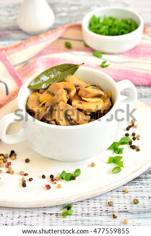 Salad with mushrooms in a white bowl on a light wooden background