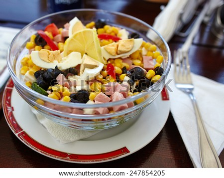 Salad with olives, pepper, ham, cheese and boiled eggs in a bowl - stock photo
