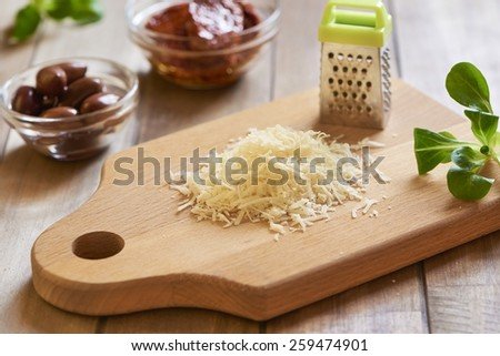 Salad with parmesan chips, dried tomatoes and olives. Cooking process. Step 2. Grated cheese for chips - stock photo