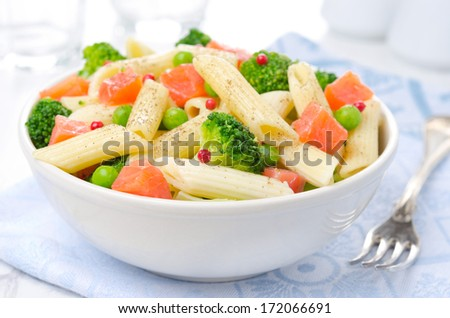 salad with pasta, smoked salmon, broccoli and green peas in a white bowl - stock photo
