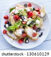 Salad with pita bread, cherry tomatoes, basil, red onion and olives served with breaded chicken and feta cheese - stock photo