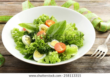 Salad with quail egg and basil in plate on rustic wooden table background - stock photo