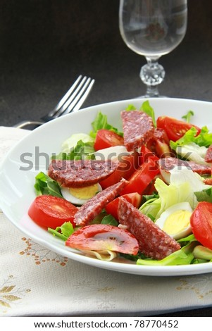 salad with quail eggs and salami on a plate