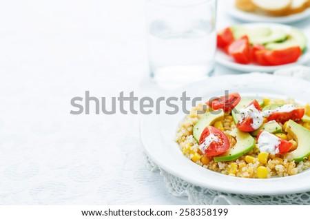salad with quinoa, red lentils, corn, avocado and tomato with yogurt sauce. tinting. selective focus - stock photo