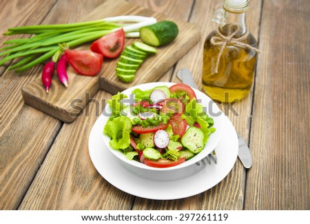 Salad with radishes and fresh vegetables on a wooden table - stock photo