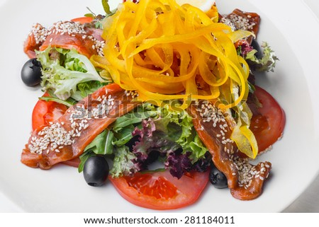 Salad with raw salmon. Sliced fresh tomatoes, black olives, baby mix salad, and pieces of raw salmon, topped with olive oil, savory soy sauce, shaved yellow pepper. - stock photo