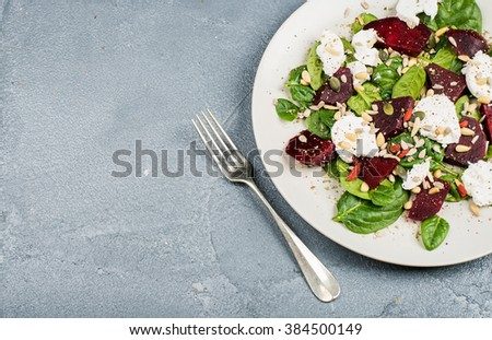 Salad with roasted beetroot, spinach, soft goat cheese and seeds in light plate over grey concrete textured background. Top view, copy space - stock photo