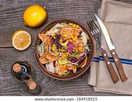 Salad with roasted spiced chicken fillet, mixed green, carrot, celery, sweet corn and lemon sauce on the wooden table, top view - stock photo